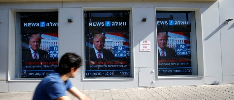 A man cycles past images of newly elected U.S. President Donald Trump which are displayed on monitors in Tel Aviv, Israel November 9, 2016. REUTERS/Baz Ratner