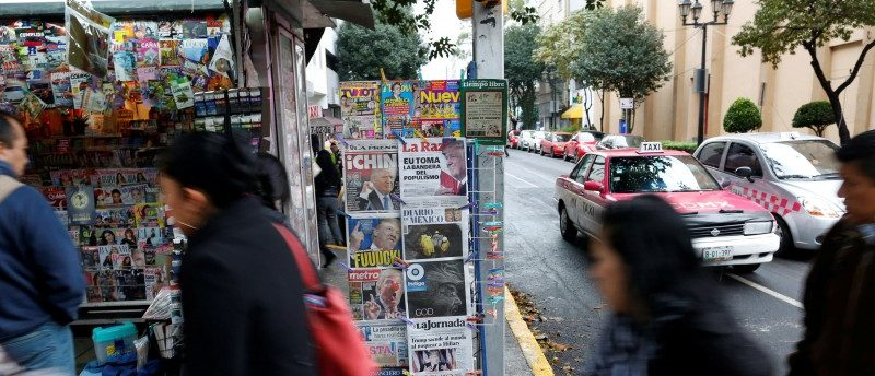 People walk past a newspaper stand in Mexico City, Mexico, November 9, 2016. REUTERS/Carlos Jasso
