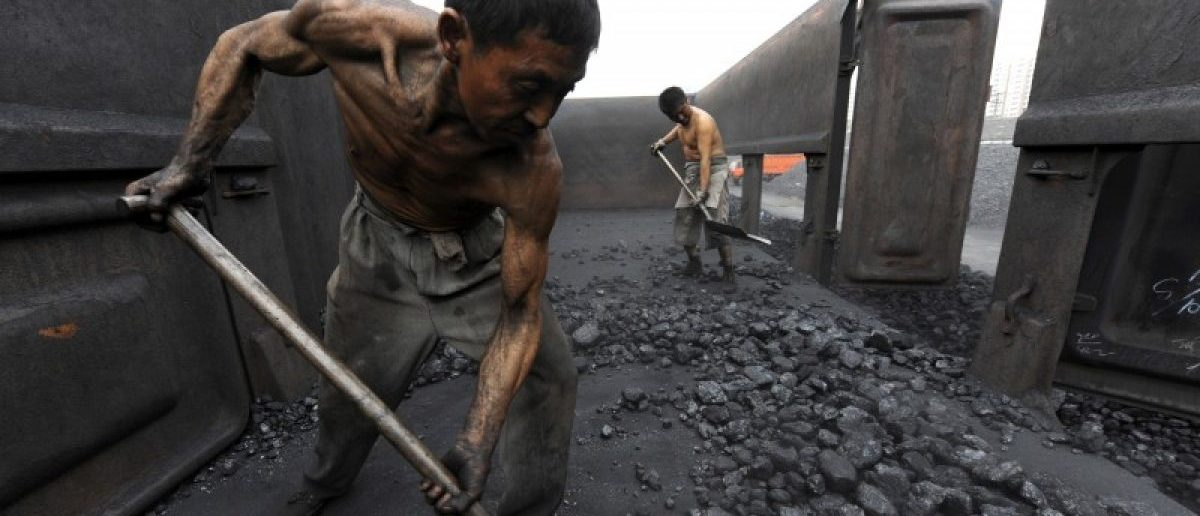 Workers unload coal at a storage site along a railway station in Hefei,