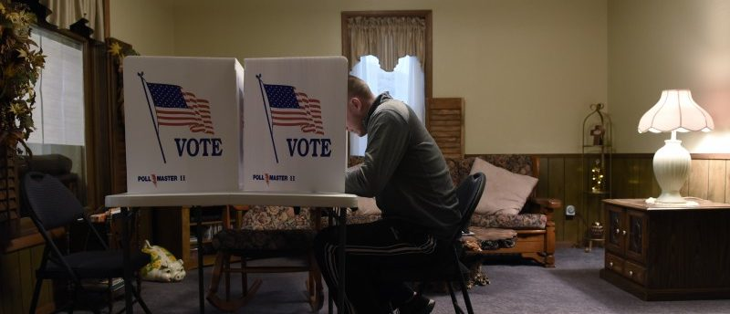 A voter fills out his ballot in a living room polling place during the U.S. presidential election in Dover, Oklahoma