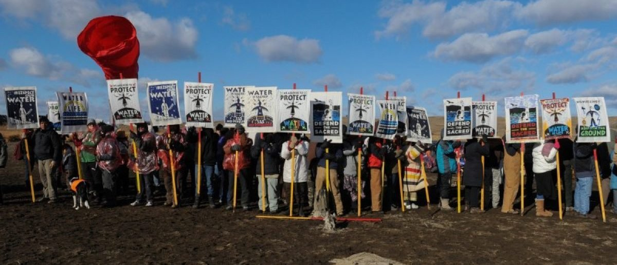 Protesters hold signs during a protest against plans to pass the Dakota Access pipeline near the Standing Rock Indian Reservation, near Cannon Ball, North Dakota, U.S. November 18, 2016.