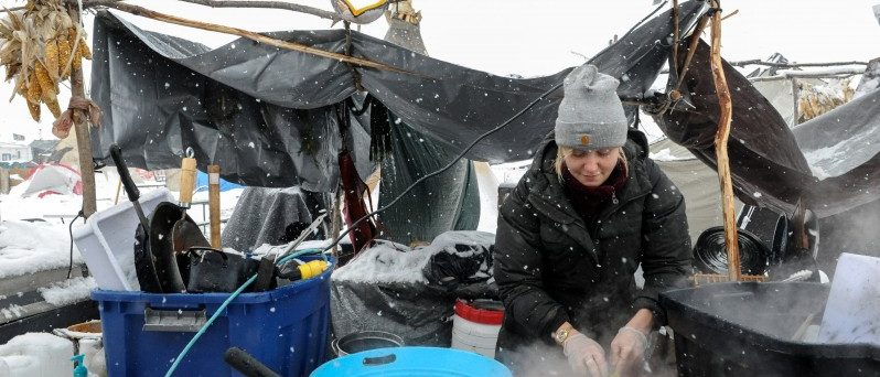 A woman washes dishes in the Oceti Sakowin camp in a snow storm during a protest against plans to pass the Dakota Access pipeline near the Standing Rock Indian Reservation, near Cannon Ball, North Dakota, U.S. November 28, 2016. REUTERS/Stephanie Keith