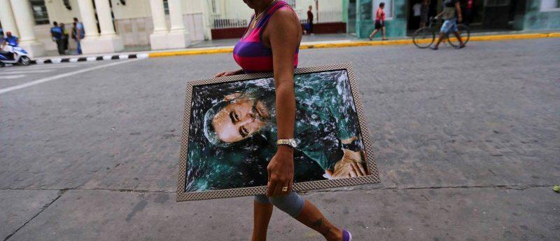 A woman carries a portrait of Cuba's late President Fidel Castro in Santa Clara, Cuba, November 30, 2016. REUTERS/Ivan Alvarado