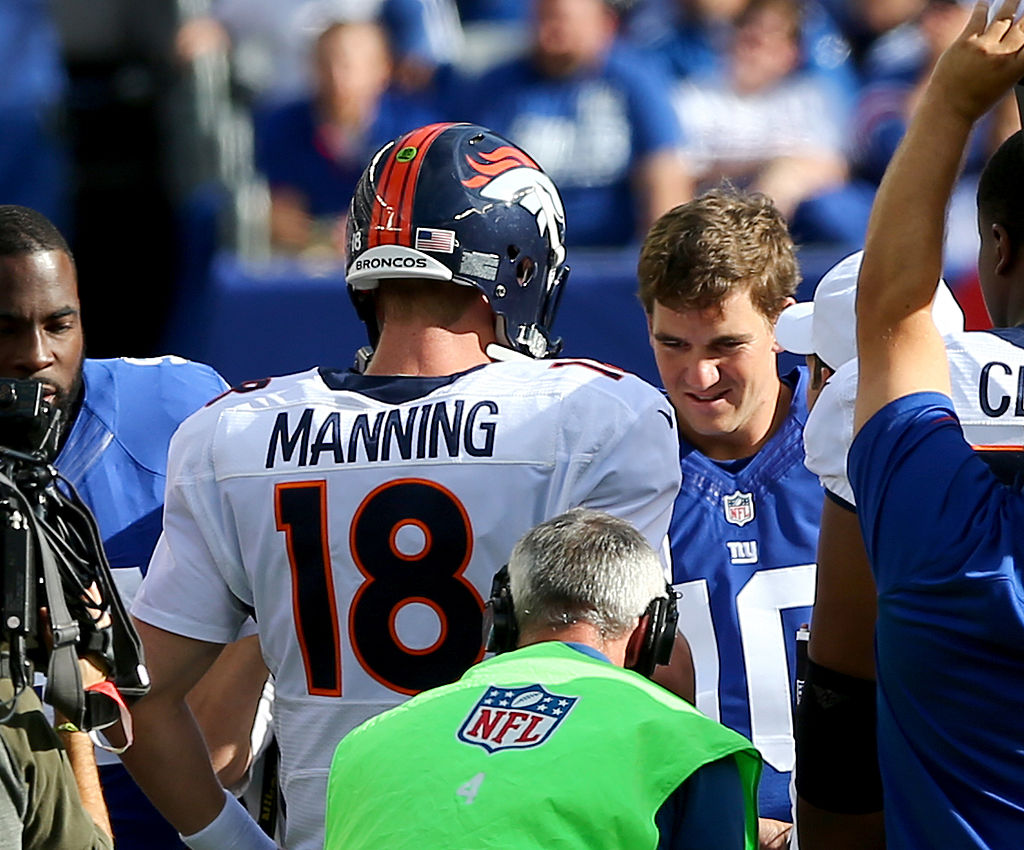 Peyton Manning #18 of the Denver Broncos and Eli Manning #10 of the New York Giants meet for the coin toss in the center of the field . (Photo by Elsa/Getty Images)