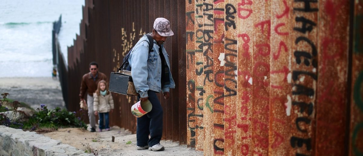 A man walks along the U.S.-Mexico border wall on February 22, 2015 in Tijuana, Mexico. (Sandy Huffaker/Getty Images)