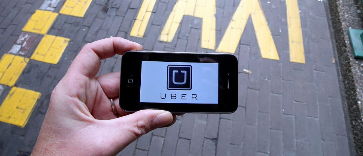 The logo of Uber car service app is seen on a smart phone during a protest by Brussels taxi drivers against the taxi-app Uber, on September 13, 2015, in Brussels. (Photo credit: NICOLAS MAETERLINCK/AFP/Getty Images)