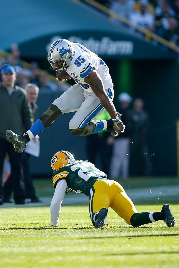 Eric Ebron hurdles over a Green Bay Packer defenseman. (Photo credit: Getty Images)