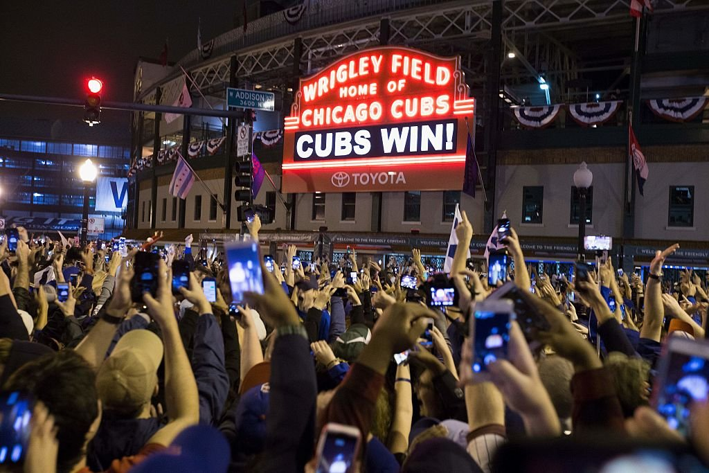 Chicago fans celebrate the Chicago Cubs 8-7 victory over the Cleveland Indians in Cleveland in 10th inning in game seven of the 2016 World Series, outside Wrigley Field in Chicago. (Photo credit: TASOS KATOPODIS/AFP/Getty Images)