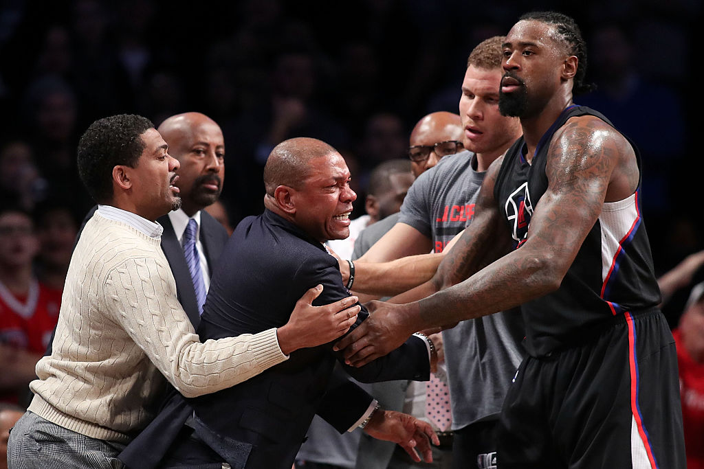 Head coach Doc Rivers of the Los Angeles Clippers is held back by DeAndre Jordan #6 and Blake Griffin #32 after a technical foul call. (Photo by Michael Reaves/Getty Images)