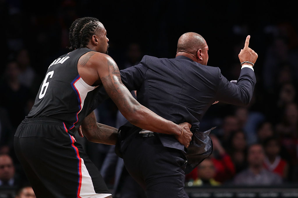 Head coach Doc Rivers of the Los Angeles Clippers is held back by DeAndre Jordan #6 after a technical foul call. (Photo by Michael Reaves/Getty Images)