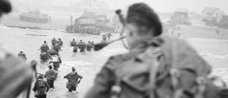 Landing on Sword Beach; Millin is in the foreground at the right; Lovat is wading through the water to the right of the column