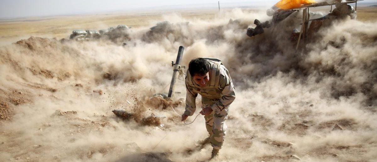 A Kurdish Peshmerga fighter launches mortar shells (REUTERS/Ahmed Jadallah)