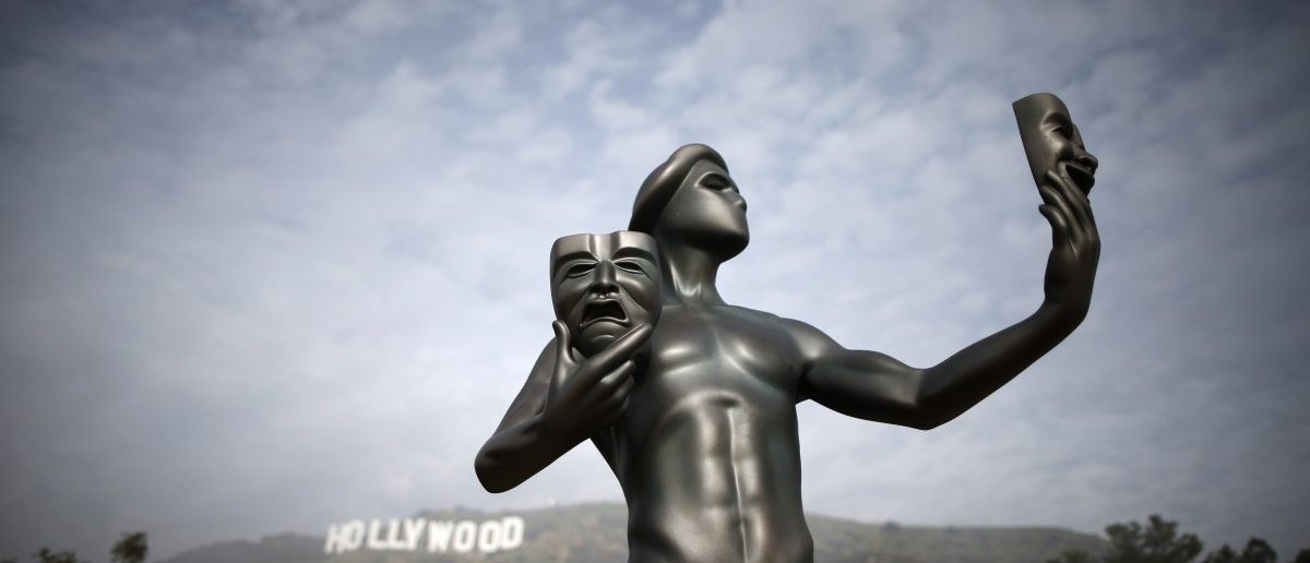 A Screen Actors Guild statue is seen in front of the Hollywood sign in Los Angeles, California January 20, 2015. REUTERS/Lucy Nicholson