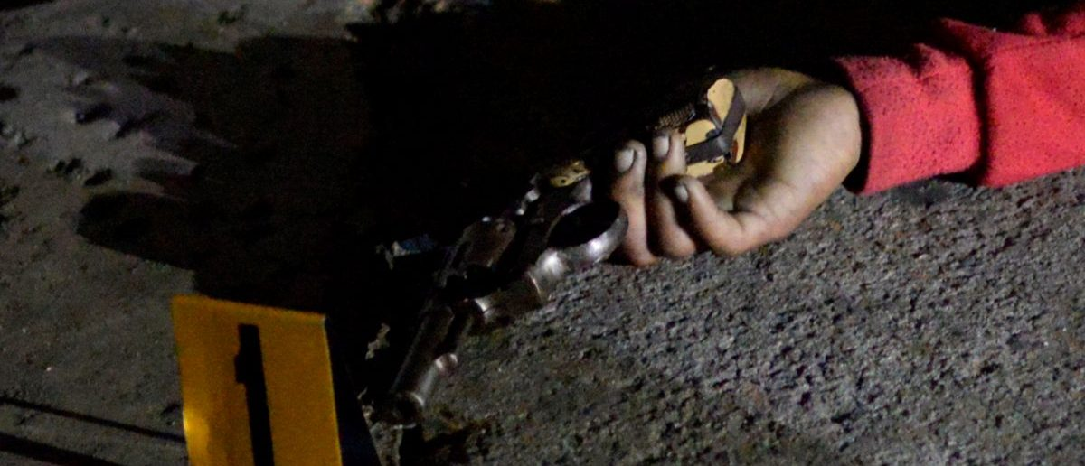 A revolver is seen in the hand of one of the three bodies of men lying on a street, who police said were gunned down in an armed encounter by policemen at a police checkpoint in Manila, Philippines September 21, 2016. REUTERS/Ezra Acayan