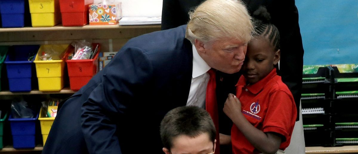 Republican presidential nominee Donald Trump hugs a student after receiving a bible as a gift during a campaign visit to the International Church of Las Vegas and the International Christian Academy in Las Vegas, Nevada, U.S., October 5, 2016. REUTERS/Mike Segar