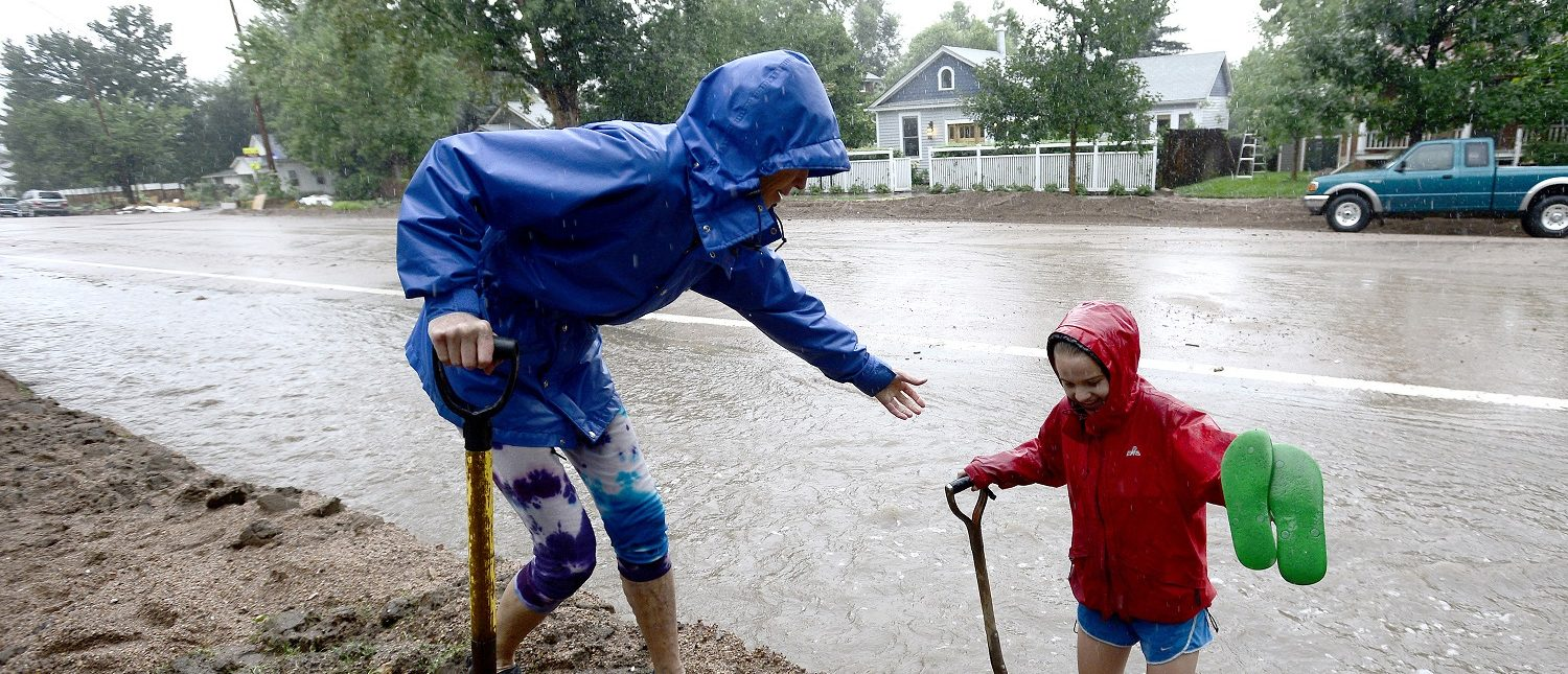 Wendy Hoffenberg helps Sophia Cornell up the side walk as rain starts getting heavier during the near Biblical amount of rain that hit Colorado in 2013. This is Boulder, but several counties, including Greeley, were essentially demolished. REUTERS/Mark Leffingwell