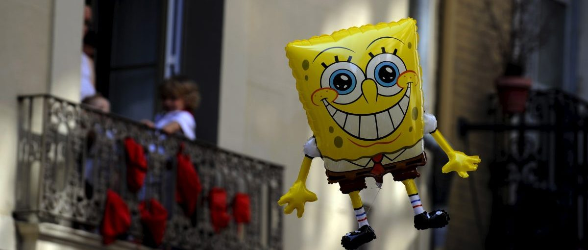 """ATTENTION EDITORS: SPANISH LAW REQUIRES THAT THE FACES OF MINORS ARE MASKED IN PUBLICATIONS WITHIN SPAIN A balloon in the shape of SpongeBob SquarePants floats near balconies during a procession in honour of San Fermin at the San Fermin festival in Pamplona, northern Spain, July 7, 2015. A statue dating from the fifteenth century is paraded through the streets of the town in honour of the patron saint of Navarra and first bishop of Pamplona, and """"Jotas"""" are sung and played in his honour. San Fermin is believed to protect the hundreds of runners that participate in the running of the bulls. REUTERS/Eloy Alonso - RTX1JEF1"""