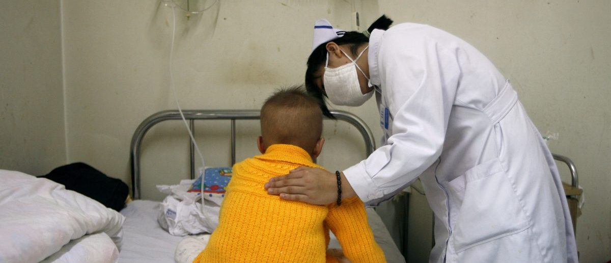 A nurse comforts a three-year-old patient in the HIV/AIDS ward of the Beijing YouAn Hospital October 28, 2008. REUTERS/David Gray