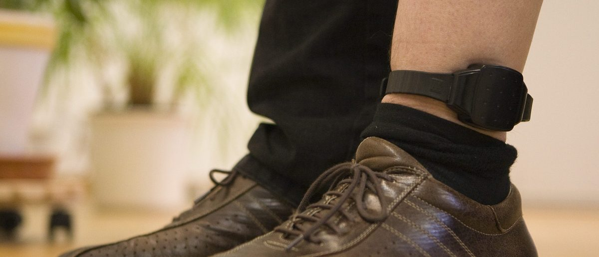 An official demonstrates the wearing of an electronic monitoring ankle-bracelet. REUTERS/Michael Buholzer