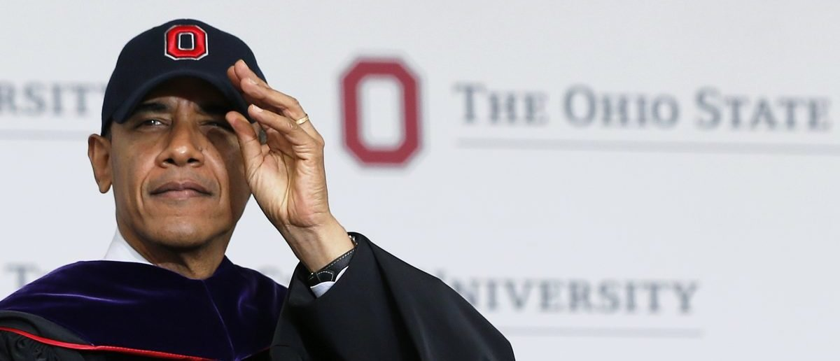 Barack Obama dons an Ohio State University cap (REUTERS/Jason Reed)
