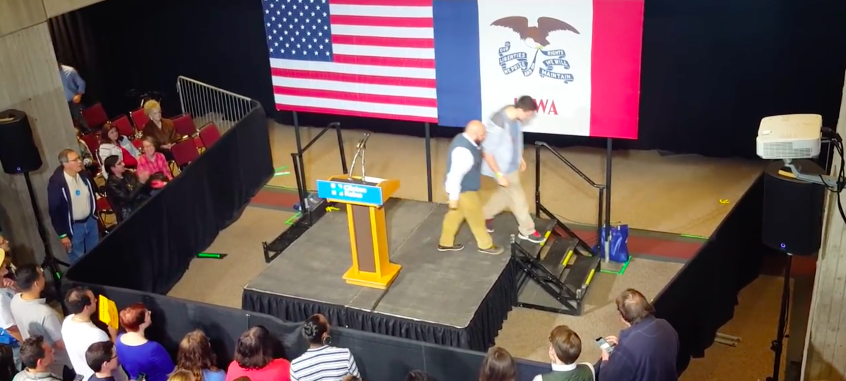 Kaleb Vanfosson is escorted off stage at a rally for Hillary Clinton after attacking the candidate. Screen capture from YouTube