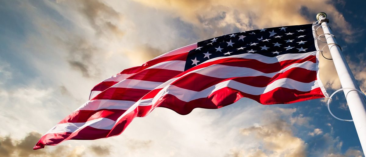 An American flag against a sky background. (Green/Shutterstock).