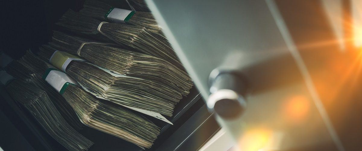 Stacks of cash in a safety deposit box. (Welcomia/Shutterstock).