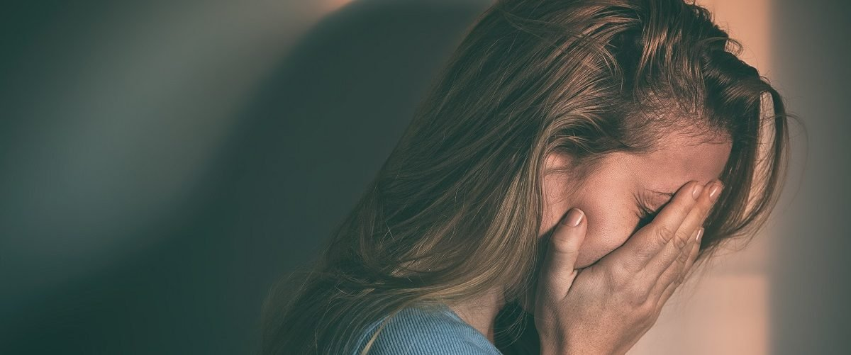 Suicidal woman cries alone. (Marjan Apostolovic/Shutterstock).