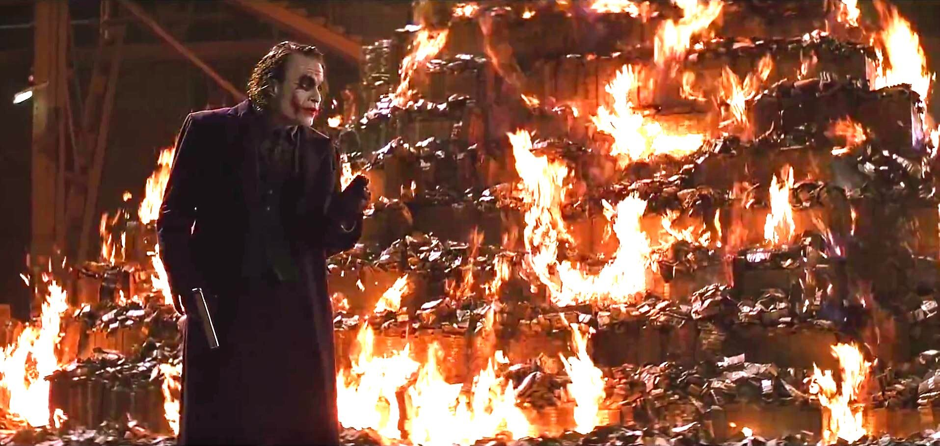 Joker stands in front of a bonfire of cash. (YouTube screengrab)