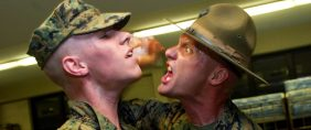 United States Marine Corps drill instructor yells at a recruit after wakeup