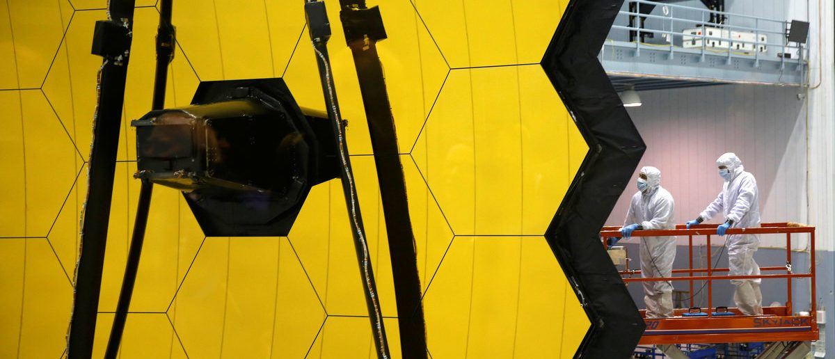 NASA workers are lifted alongside the James Webb Space Telescope Mirror during it's media reveal at NASA's Goddard Space Flight Center at Greenbelt, Maryland, U.S., November 2, 2016. (REUTERS/Kevin Lamarque)