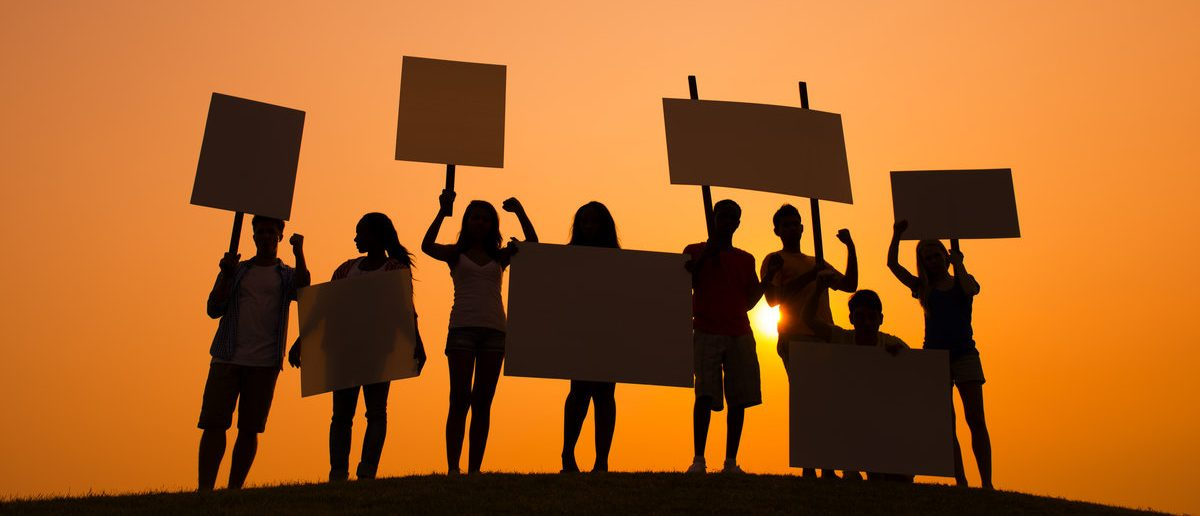 Silhouette of People Protesting at Sunset (Shutterstock/Rawpixel.com)