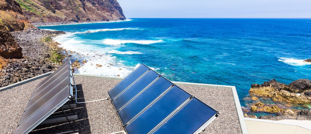 Blue solar panels on roof at sea (Shutterstock/Bildagentur Zoonar GmbH)