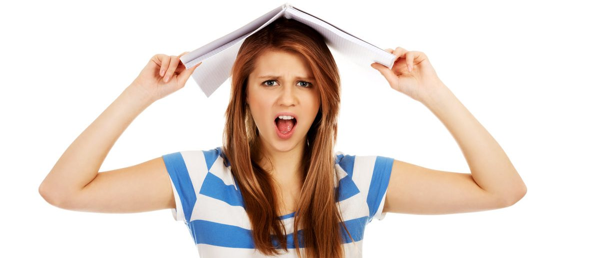 Screaming college student woman with notebook on head (Shutterstock/Piotr Marcinski)