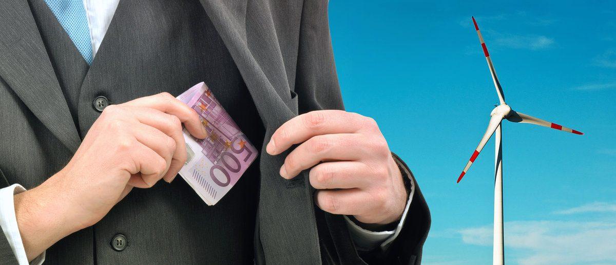 Businessman pocketing money from wind turbine (Shutterstock/igorstevanovic)