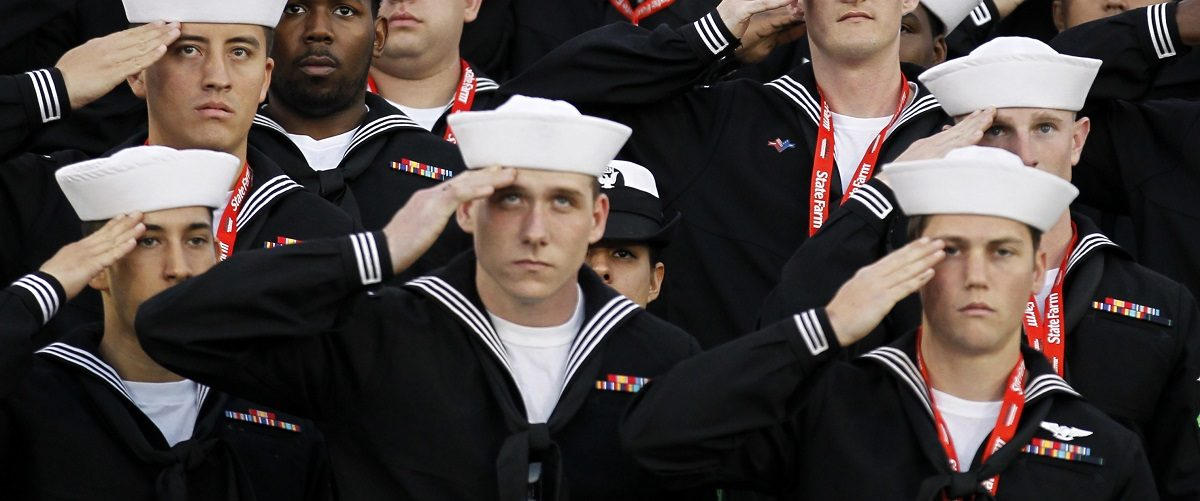 U.S. sailors salute during the retiring of the colors during the NCAA Carrier Classic men's college basketball game between Michigan State Spartans and North Carolina Tar Heels in Coronado,