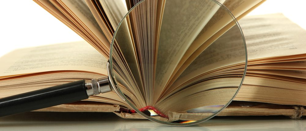 Magnifying glass and open book (Photo: Africa Studio/Shutterstock)