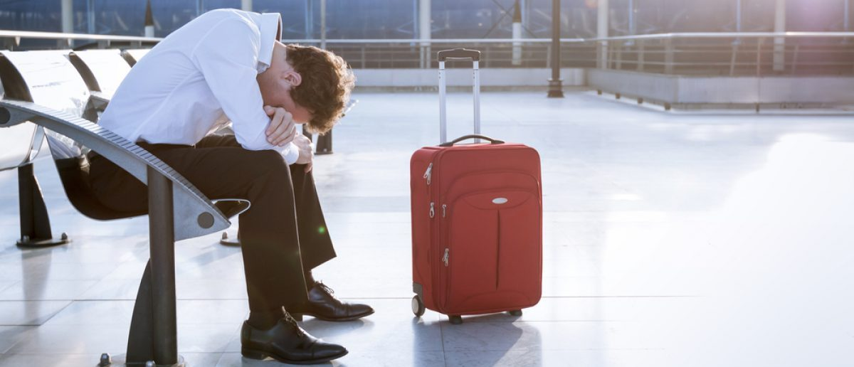 Depressed traveler waiting at airport after flight delays and cancellations. [Shutterstock - NicoElNino]