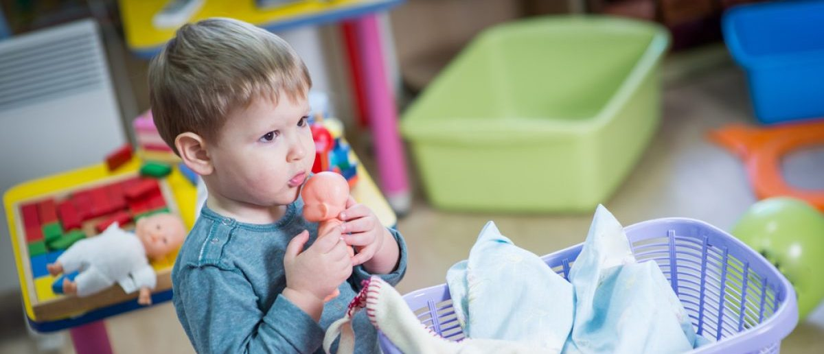 Young boy plays with a doll (Photo via Shutterstock)