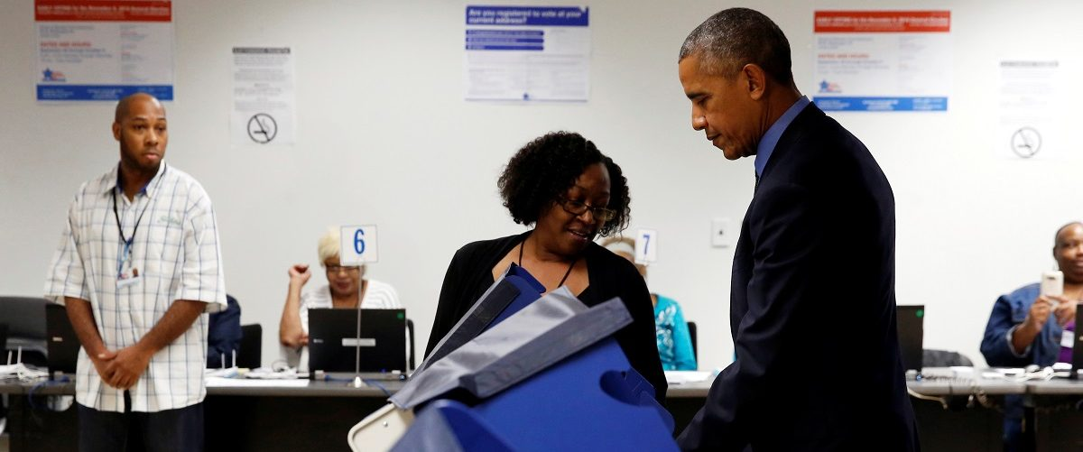 A poll worker assists U.S. President Barack Obama as he prepares to cast his vote for president in early voting at the Cook County Office Building in Chicago, Illinois, U.S. October 7, 2016. REUTERS/Jonathan Ernst.