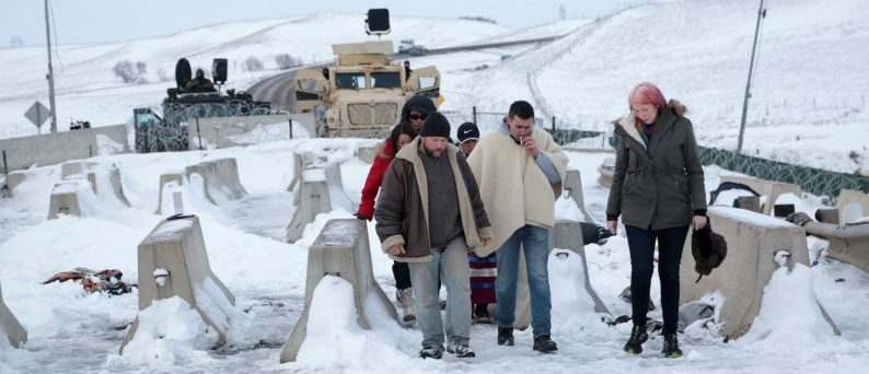 Wesley Clark Jr. (2nd R) talks with opponents of the Dakota Access oil pipeline and local law enforcement on Backwater Bridge near Cannon Ball, North Dakota, U.S., December 2, 2016. REUTERS/Terray Sylvester