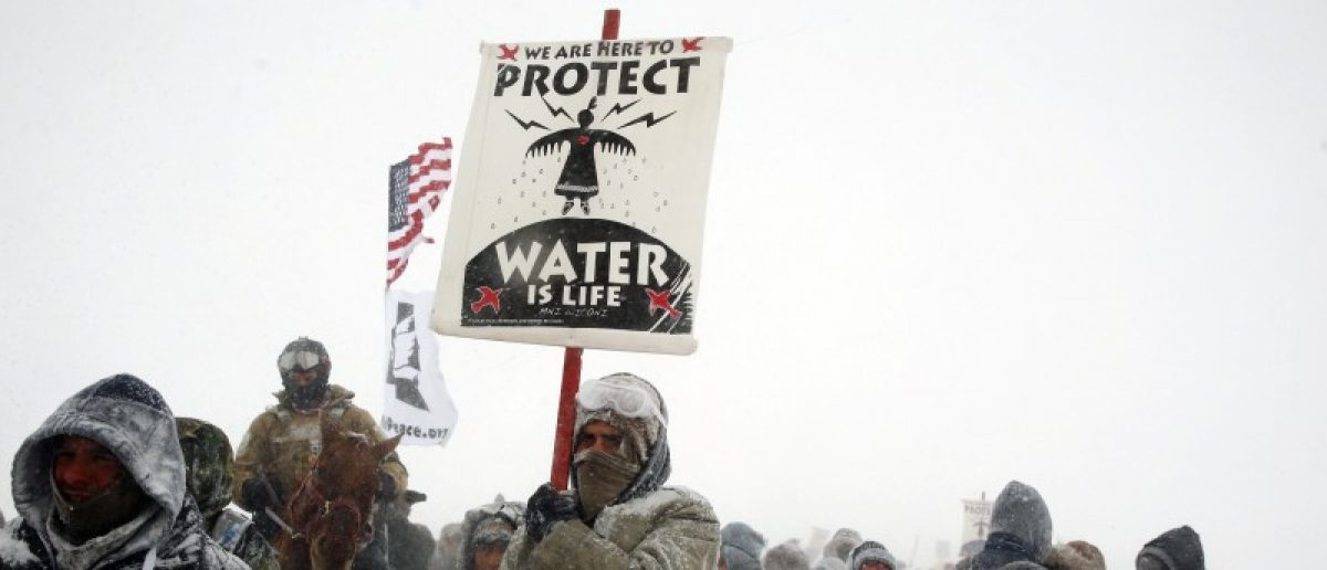 "Veterans join activists in a march just outside the Oceti Sakowin camp during a snow fall as ""water protectors"" continue to demonstrate against plans to pass the Dakota Access pipeline adjacent to the Standing Rock Indian Reservation, near Cannon Ball, North Dakota, U.S., December 5, 2016."