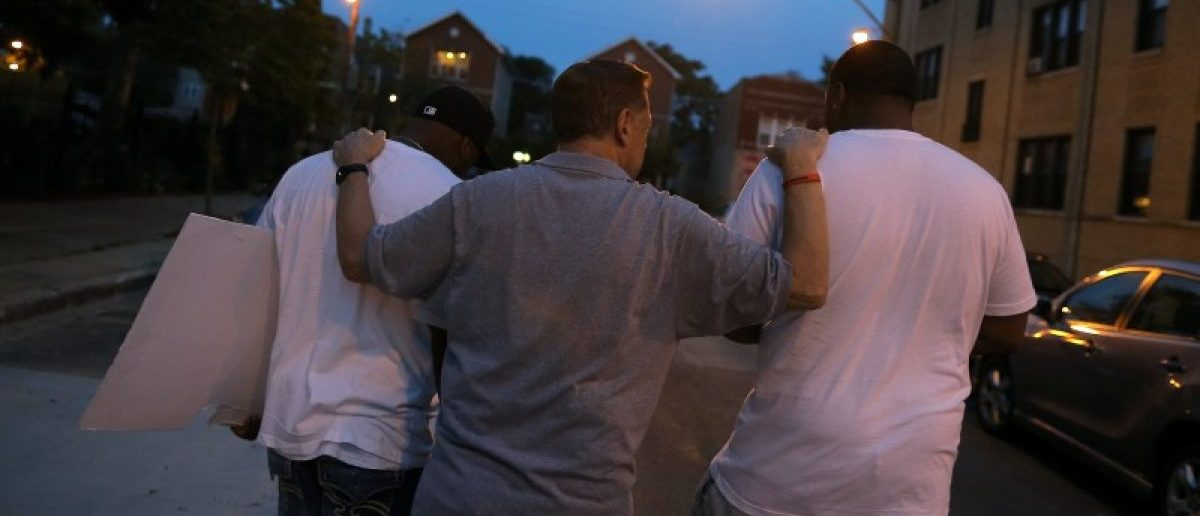Father Michael Pfleger (C) speaks with participants in a weekly night-time peace march through the streets of a South Side neighborhood in Chicago, Illinois, September 16, 2016. REUTERS/Jim Young