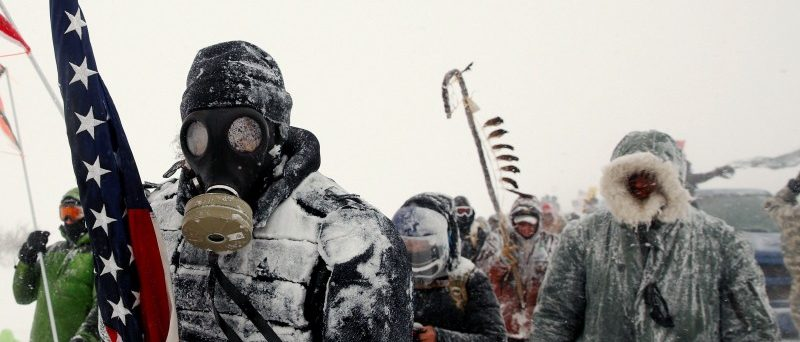 """A man takes part in a march with veterans to Backwater Bridge just outside of the Oceti Sakowin Camp during a snow fall as """"water protectors"""" continue to demonstrate against plans to pass the Dakota Access pipeline adjacent to the Standing Rock Indian Reservation, near Cannon Ball, North Dakota, U.S., December 5, 2016. REUTERS/Lucas Jackson/File Photo"""