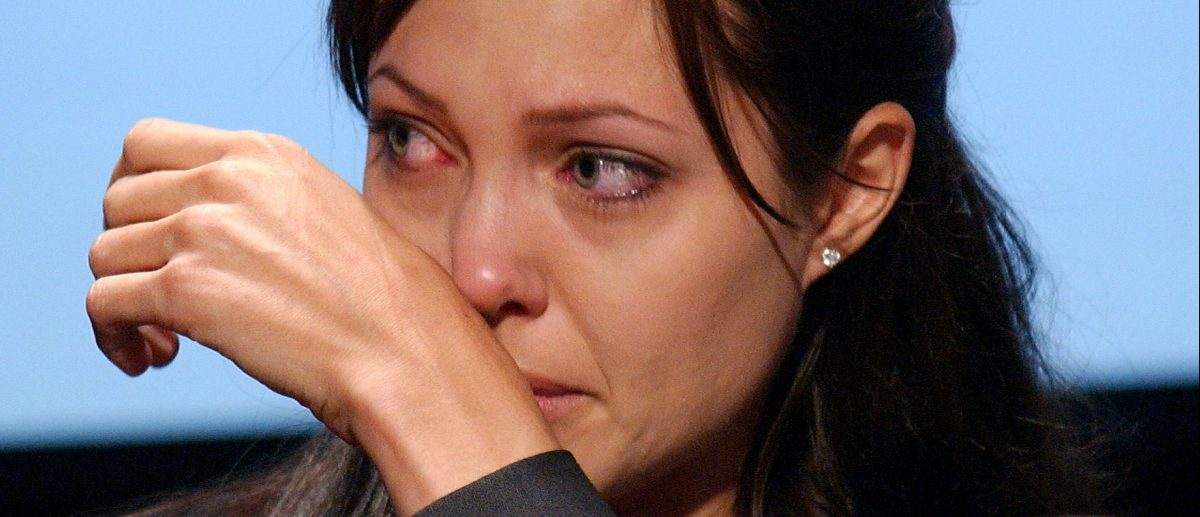 Angelina Jolie, Goodwill Ambassador for the United Nations High Commission for Refugees (UNHCR), cries during a World Refugee Day ceremony June 20, 2003 in Washington, D.C. (Photo by Stefan Zaklin/Getty Images)