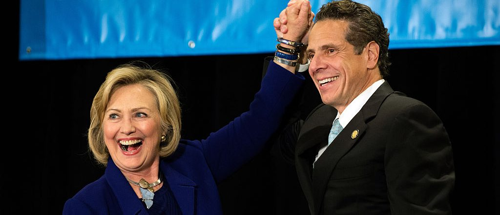 "NEW YORK, NY - OCTOBER 23: Former U.S. Secretary of State and U.S. Sen. Hillary Rodham Clinton (left to right) raises the hand of incumbent New York Governor Andrew Cuomo laugh during a ""Women for Cuomo"" campaign event on October 23, 2014 at the Grand Hyatt Hotel in New York, NY. Cuomo was joined by Clinton who, citing his record on women's rights, endorsed him in the upcoming gubernatorial election on November 4, 2014. U.S. Rep. Kathy Hochul, the Democratic nominee for New York Lt. Gov., also spoke at the event. (Photo by Bryan Thomas/Getty Images)"