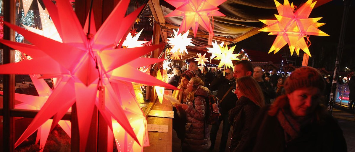 Visitors walk past a stall selling illuminated stars at the annual Christmas market at Alexanderplatz on November 24, 2015 in Berlin, Germany. Christmas markets are opening across Germany this week as Europe remains tense following the recent terror attacks in Paris and the continued manhunt for those involved.  (Photo by Sean Gallup/Getty Images)
