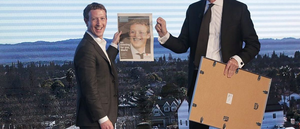 Facebook founder and chief Mark Zuckerberg (L) receives a newspaper from Springer CEO Mathias Doepfner during the Axel Springer Award in Berlin on February 25, 2016. (Photo credit: KAY NIETFELD/AFP/Getty Images)