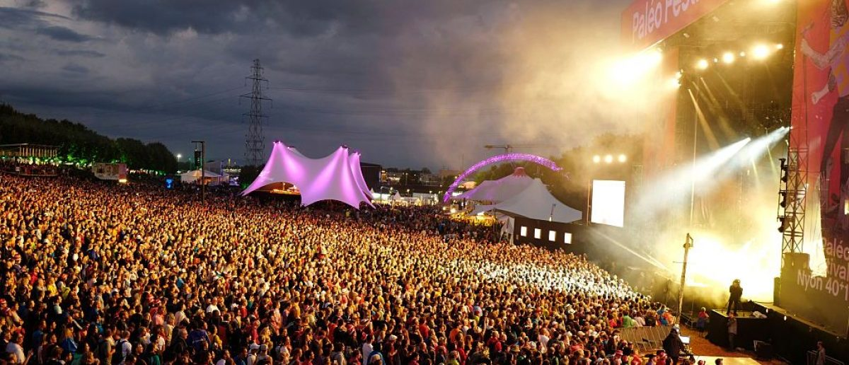 Festival goers attend a concert at the main stage during the 41st edition of Paleo on late July 23, 2016 in Nyon, one of the Swiss largest open-air music festival. (Photo credit: FABRICE COFFRINI/AFP/Getty Images)