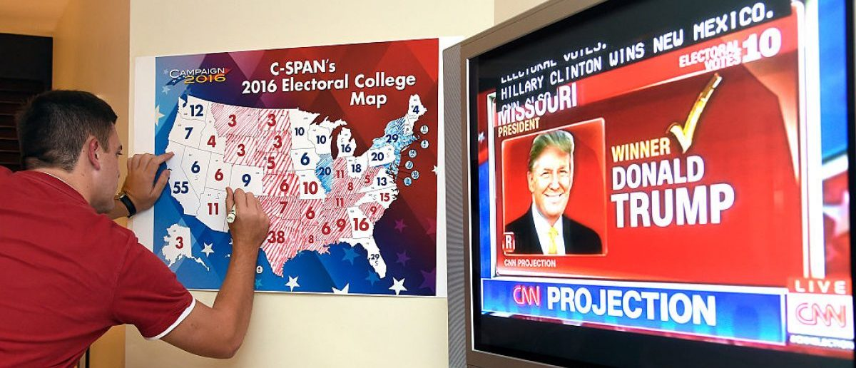 Jake Krupa colors in an electoral map as states projected for Republican presidential candidate Donald Trump or Democratic Presidential candidate Hillary Clinton at an election watching party in Coconut Grove, Florida, on November 8, 2016. / AFP / RHONA WISE (Photo credit should read RHONA WISE/AFP/Getty Images)